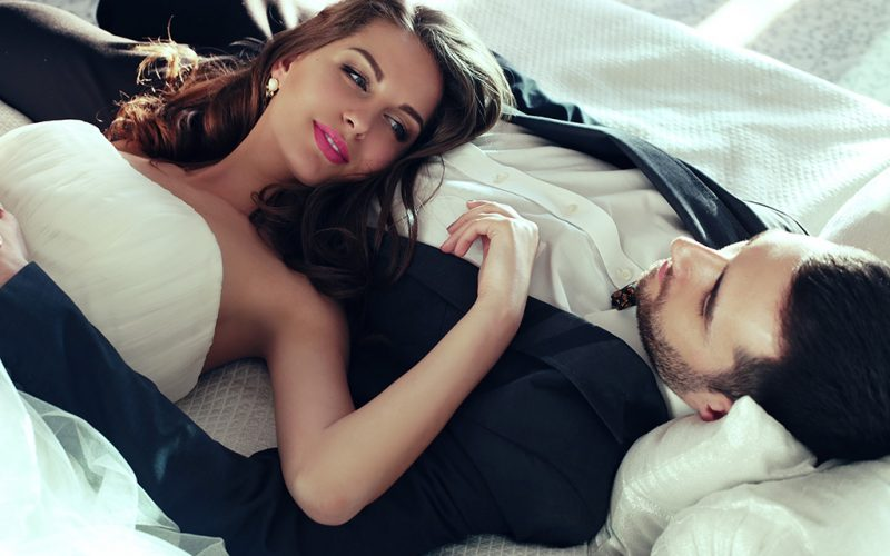 fashion interior photo of beautiful tender couple, groom and bride wear wedding clothes,embracing  in bedroom